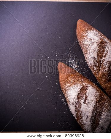 Rustic bread roll or french baguette and flour on black background with free text space.