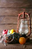 pic of kerosene lamp  - Kerosene lamp with beads and fruits on wooden planks background - JPG