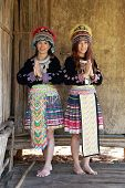 stock photo of hmong  - Traditionally dressed Mhong hill tribe woman pay respect at the wooden cottage - JPG