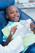 stock photo of dentist  - Dentist teaching happy boy how to brush teeth in the dentists chair - JPG
