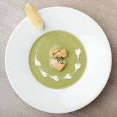 stock photo of water cabbage  - Green cabbage broccoli cream soup puree in white plate served with filleted salmon pieces lemon and theme - JPG