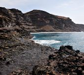 stock photo of off-shore  - The rugged volcanic coastline and shores of the island of Fogo Part of the archipelago of Cape Verde off the west coast of Africa