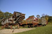 stock photo of threshing  - An old threshing machine and hayracks are lined up waiting for the harvest of the the crops - JPG