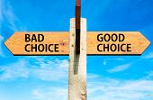 stock photo of opposites  - Wooden signpost with two opposite arrows over clear blue sky Bad Choice and Good Choice messages Right choice conceptual image - JPG