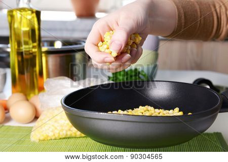 Woman cooking corn in kitchen close up