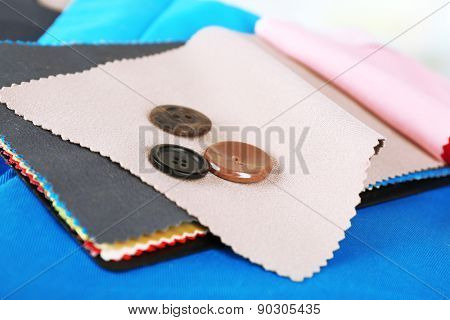 Colorful fabric samples and buttons on light blurred background