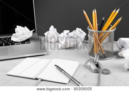Working mess with crumpled paper and notebook on wooden table and dark background