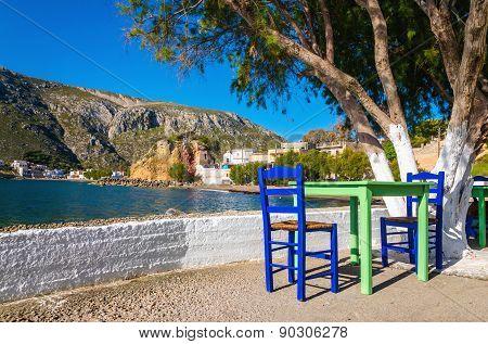 Green table, chairs in romantic Greek bay, Greece