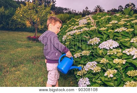 Happy boy watering flowers in the garden