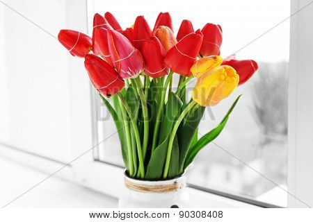 Bouquet of fresh tulips on windowsill background