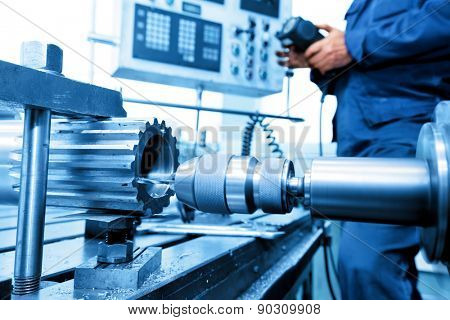 Man operating CNC drilling and boring machine in workshop. Industry, industrial concept.
