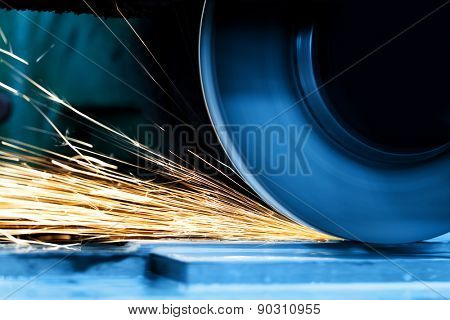 Sparks from grinding machine in workshop. Industrial background, industry.