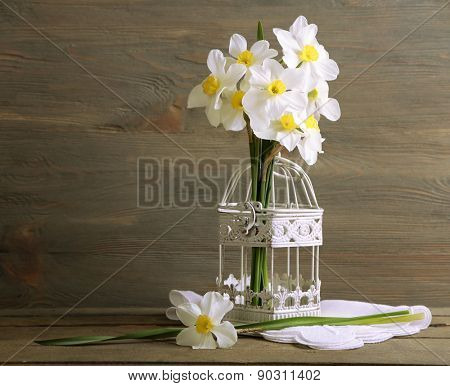 Fresh narcissus in decorative cage on wooden background