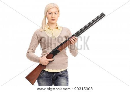 Serious girl holding a shotgun isolated on white background
