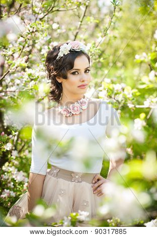 Portrait of beautiful girl posing outdoor with flowers of the cherry trees in blossom