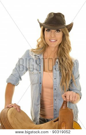 Cowgirl Standing By Saddle Holding Onto Horn Smiling