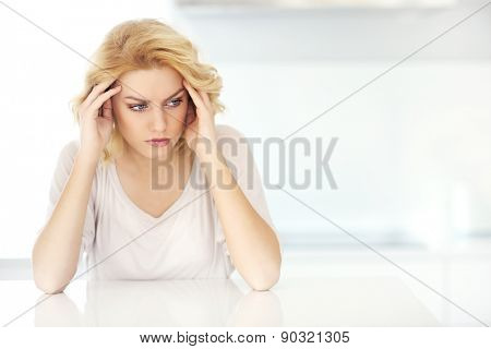 A picture of an adult woman having headache at home