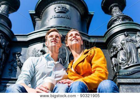 Tourist couple sitting in Dresden Theaterplatz in front of statue