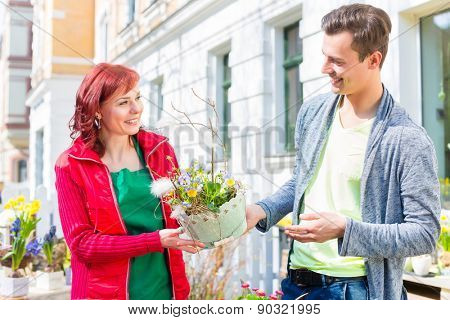 Female florist selling man plant in front of flower shop