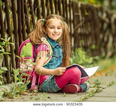 Little pretty schoolgirl reading a book sitting on the street