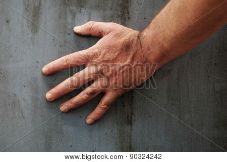 Male hand touching the gray grunge surface of a stained concrete wall, close-up