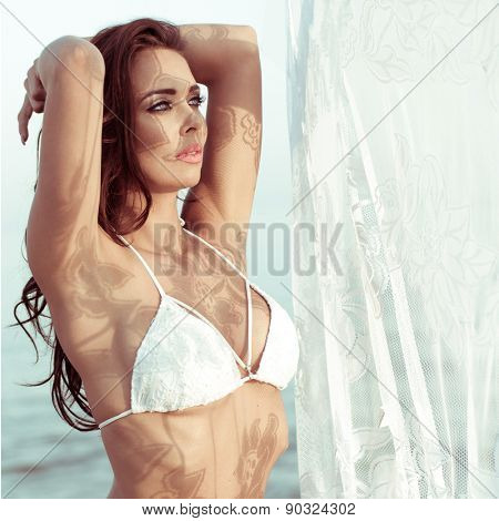 Attractive Brunette Woman Wearing White Bikini Standing with Hands Behind Head Near Lace Curtain Beside Water