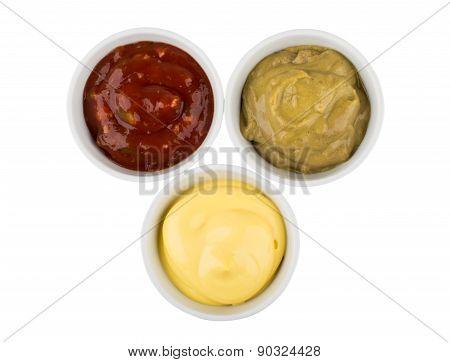 Three Small Glass Bowls With Ketchup, Mayonnaise And Mustard