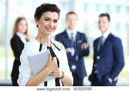 Business Woman Standing In Foreground With A Tablet In Her Hands, Her Co-workers Discussing Business