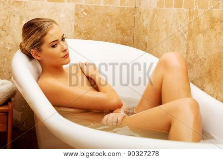 Beautiful thoughtful woman relaxing in bathtub