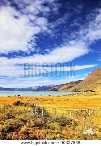 The fence placed to protect grazing cows. Lake in the high valley of the Patagonian Andes