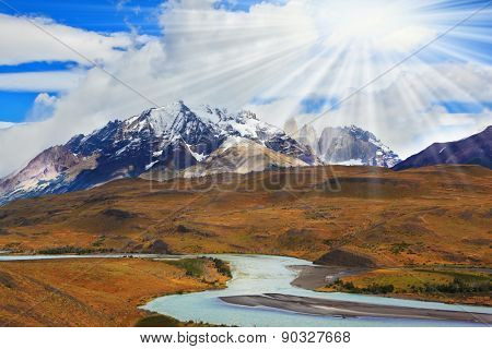 Beautiful summer morning in Patagonia.The river and the snow-capped mountains illuminated by the sun
