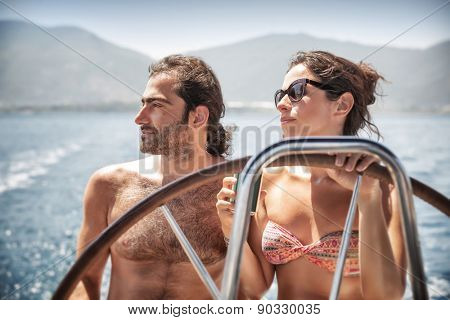 Beautiful couple on sailboat, young happy family behind helm of luxury water transport, having fun in the sea, active summer vacation concept