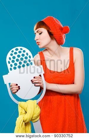 French woman wearing beret. blue background. microphone, singer,