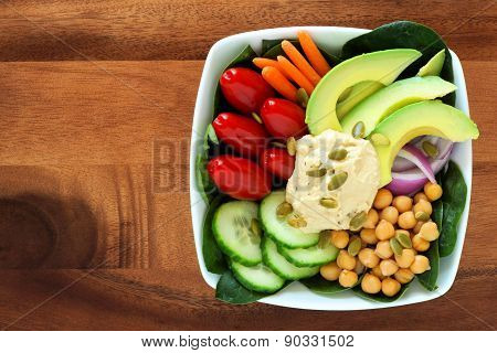 Nutritious lunch bowl with avocado, hummus and vegetables on wood