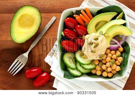 Healthy lunch bowl with avocado, hummus and fresh vegetables