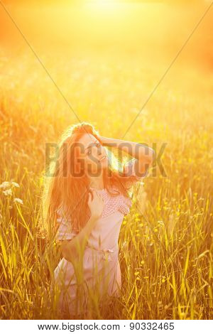 Young hipster model woman Casual Girl in field in Sunset in spring, summer landscape background Springtime Summertime. Allergic to pollen of flowers Allergy Backlit Sun Light Autumn Glow Sun Sunshine