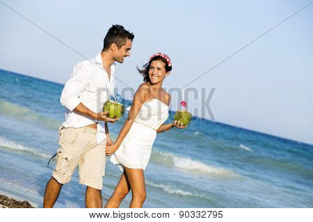 Couple enjoying their honeymoon in the Caribbean, walking while holding a coconut