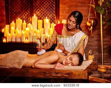 White woman having ayurvedic massage with pouch of rice. A lot of burning candles.