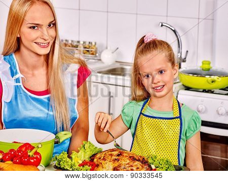 Mother and daughter cooking chiken food at kitchen.