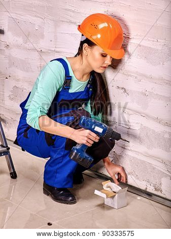 Happy family in blue builder uniform drilled wall