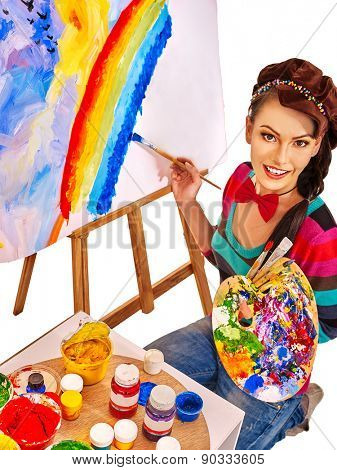 Artist woman painting on easel at work. Isolated.