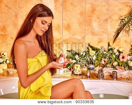 Woman applying moisturizer at bathroom. Yellow towel.