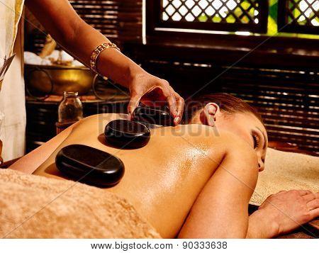 Young woman having Ayurveda black hot stone massage.
