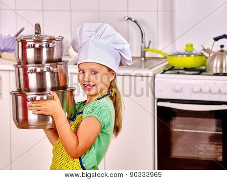 Child wearing hat and apron cooking at kitchen. A lot of pan.