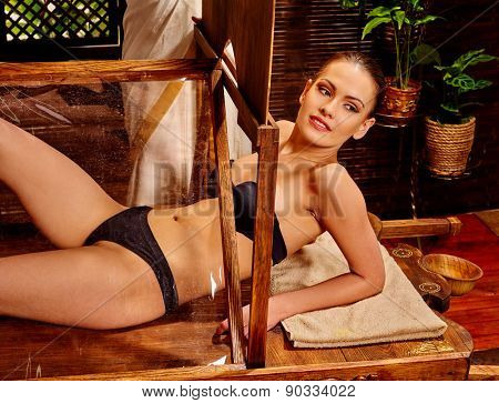 Woman having Ayurvedic wooden sauna treatment. Aromatherapy