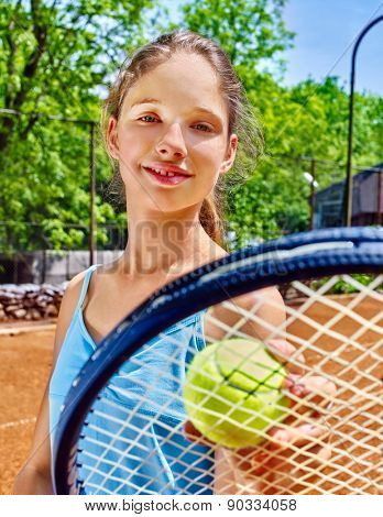 Girl sportsman with racket and ball on  tennis court. Green tree ang blue sky on background.
