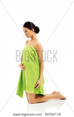 Full length woman kneeling wrapped in towel.