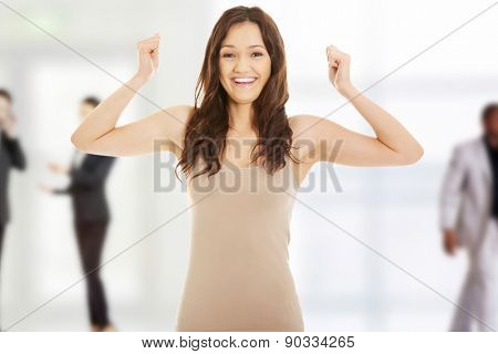 Young student woman making fists in a winner gesture.