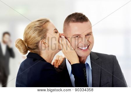 Businesswoman whispers gossip to businessman.