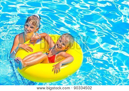 Children sitting on inflatable ring in swimming pool.